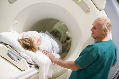 Doctor With Patient As They Prepare For A Computerized Axial Tomography (CAT) Scan